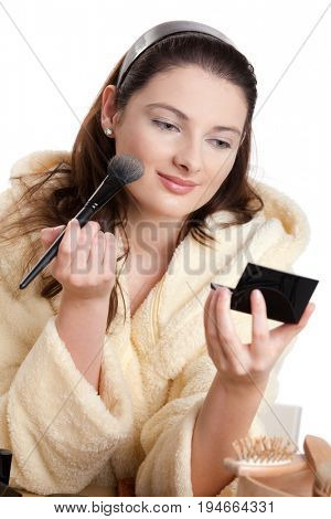 Young attractive teenager applying make-up, looking into handheld mirror, smiling. Isolated on white.