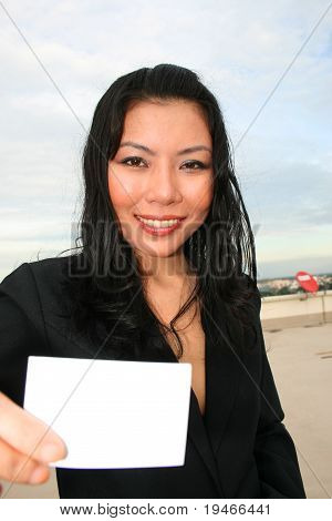 Asian woman holding white card.