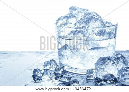 Water with crushed ice cubes in glass. Isolated on white
