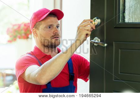 handyman in red uniform fixing house door lock