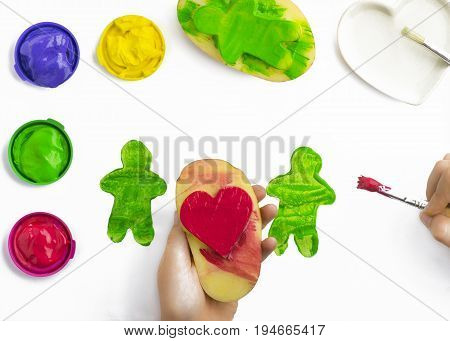 Childs hand play painting with potatoe stamps brushing red on a heart shape green yellow and purple poster paints some isolated objects on a white background
