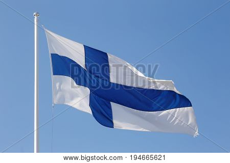 The flag of Finland on blue sky close-up.