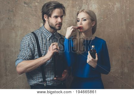 Girl drinking glass of liqueur with man. Pretty woman with blond hair and handsome macho holding bottles with alcoholic drinks on beige wall. Alcohol and convive. Unhealthy lifestyle. Bad habits
