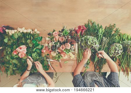 Small business. Flowers delivery shop top view. Florists creating order, making rose bouquet