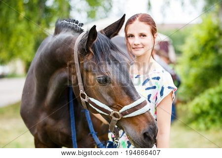 Young smiling teenage girl standing with her bay mare