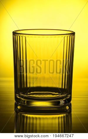 Empty faceted glass up to the light in front of the yellow light spot