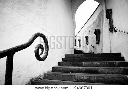 A black and white image of a stairway with handcrafted handrail lined with religeous symbols in Neuerburg Germany