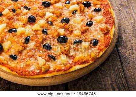 Italian pizza closeup with pineapples and black olives - thin pastry crust at wooden table background