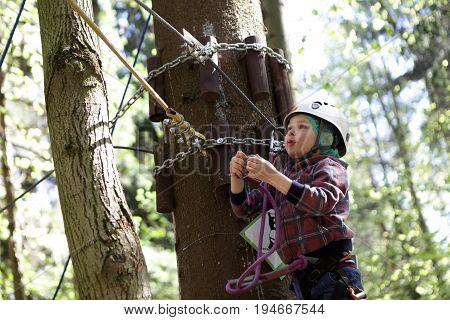 Kid Climbing In Adventure Park