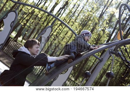 Mother helping her son climbing at playground