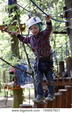 Preschooler Climbing In Adventure Park