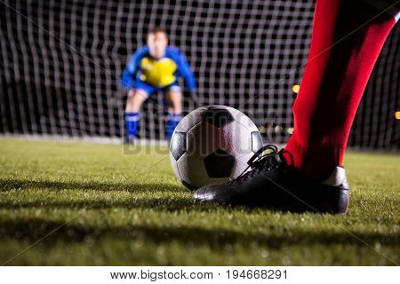 Low section of soccer player with ball against goalkeeper standing on playing field