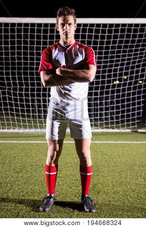 Portrait of confident male soccer player standing with arms crossed against goal post on field