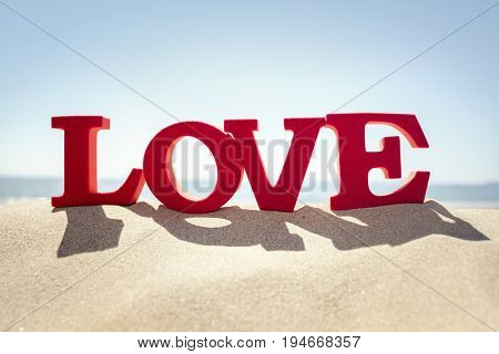 Love word on a sand beach concept for romance or romantic vacation and holiday