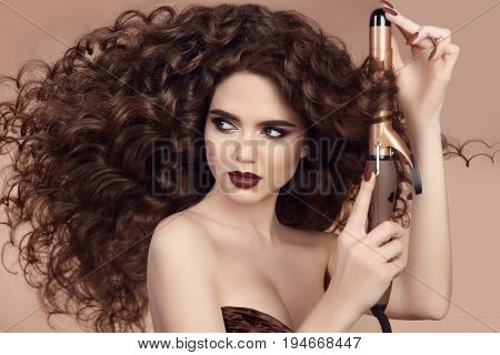 Curly Hair. Hairstyling. Beautiful Brunette Woman Portrait With Long Wavy Hair Ironing It, Using Cur