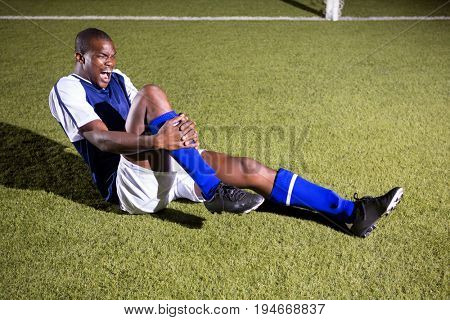 Young male soccer player shouting in agony with knee pain on playing field