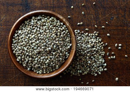 Hemp Seeds In Dark Wooden Bowl Isolated On Dark Brown Wood From Above. Spilled Hemp.