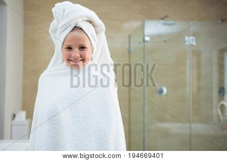Portrait of smiling girl wrapped in towel while standing in bathroom
