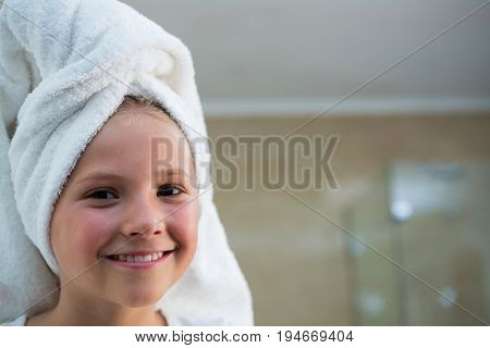 Portrait of smiling girl with hair wrapped in towel in bathroom