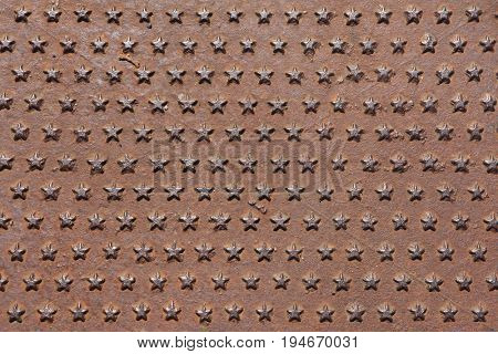 Rusted iron cast panel covered with five-pointed stars pattern. Background texture.