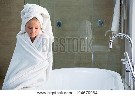 Sad girl wrapped in towel sitting on bathtub in bathroom