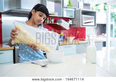 Girl pouring breakfast cereal in bowl on kitchen counter