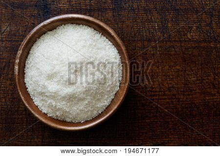 Desiccated Coconut In Dark Wooden Bowl Isolated On Dark Brown Wood From Above.