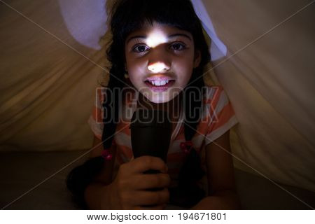 Close-up portrait of girl holding illuminated flashlight under blanket on bed at home