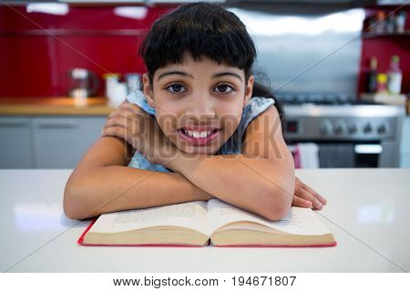 Portrait of smiling girl with arms crossed over novel in kitchen at home