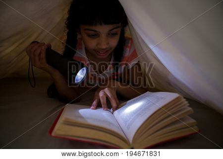 Girl holding flashlight while reading novel under blanket at home