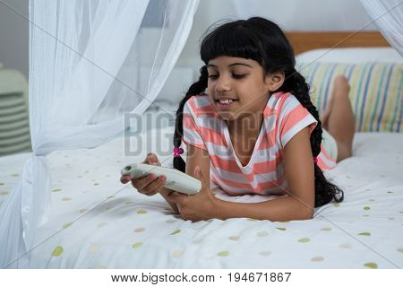 Girl pressing remote control while lying on bed at home
