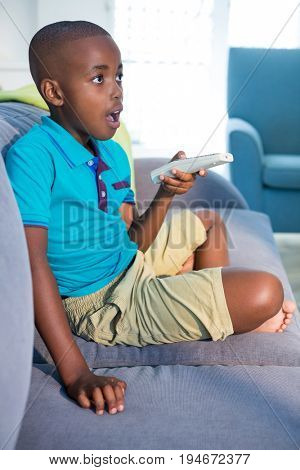 Surprised boy holding remote control while sitting on sofa in living room at home