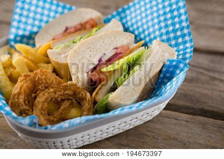 Sliced burger with French fries and onion rings in container on table