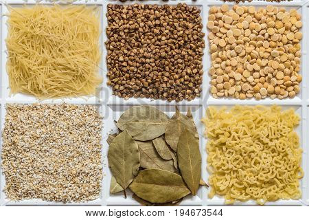 Grocery set of food products: vermicelli buckwheat dried peas barley grits bay leafs figured macaroni.