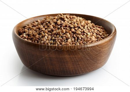 Uncooked Buckwheat In Dark Wooden Bowl Isolated On White.