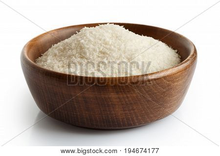 Desiccated Coconut In Dark Wooden Bowl Isolated On White.