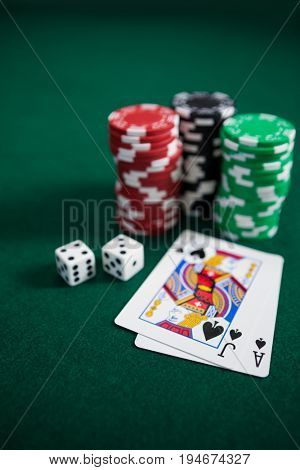 Playing cards, dices and casino chips on poker table in casino