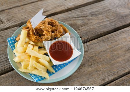 High angle view of onion rings with French fries served in plate on table