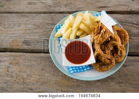 Close up of onion rings with French fries served in plate on table