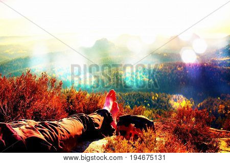 Film Grain. Long Tired Male Legs In Hiking Trousers Take A Rest On Peak Of Rock Above Valley.