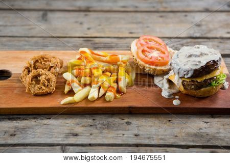 High angle view of French fries with sauce by onion rings and burger on cutting board