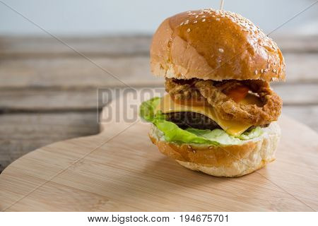 Close up of cheeseburger with onion rings on cutting board