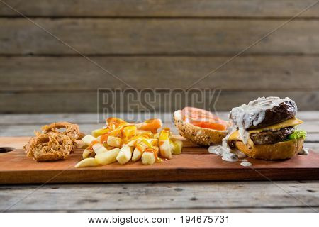 Close up of French fries with sauce and burger and onion rings on cutting board