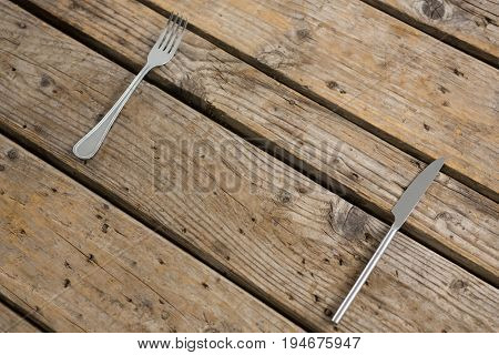 High angle view of fork and table knife on wooden table
