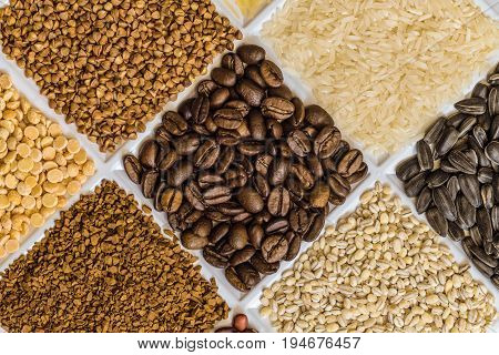 Roasted coffee beans in set of groceries with buckwheat rice sunflower seeds pearl barley freeze-dried instant coffee dried peas.