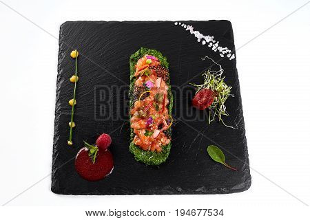 fresh salmon tartar with salt and herbs, studio shot. Fish tartar on black shale
