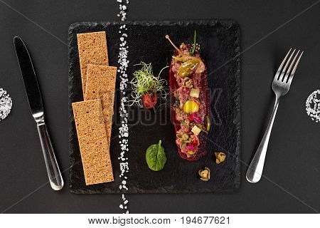 fresh beef tartar with salt and herbs and Crispbread, studio shot. Meat tartar on black shale. Top view