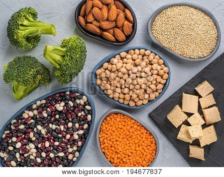 Vegetarian healthy protein sources on gray concrete background. Quinoa, chickpea, almond, red lentils, mixed bean, broccoli, tofu as vegan sources of protein concept. Close up. Top view or flat lay.