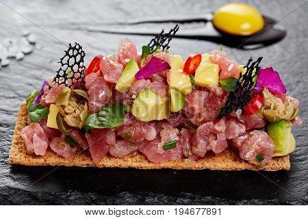 fresh tuna tartar with salt and herbs, studio shot. Fish tartar on black shale