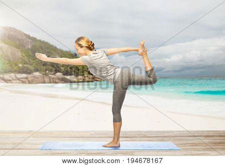 fitness, sport and healthy lifestyle concept - woman doing yoga in lord of the dance pose on mat over exotic tropical beach background